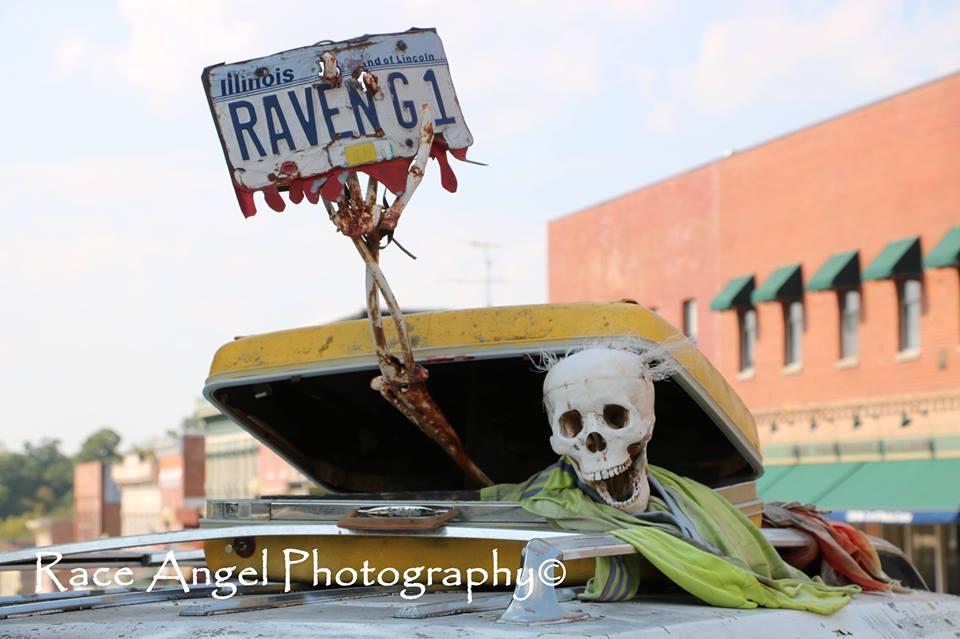 Bild von Skelett das aus einem Koffer zu steigen scheint und ein Nummernschild in der Hand hält